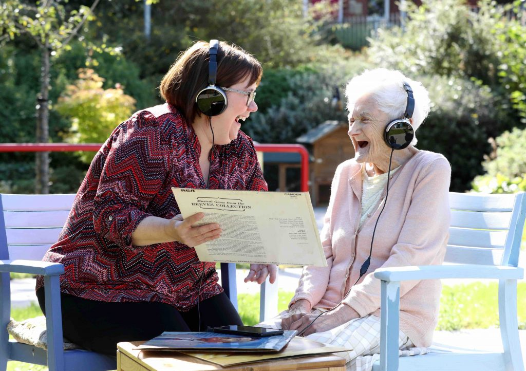 Two smiling women wearing headphones. One is holding record sleeve.